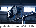 Theater spotlights on black industrial room with windows. 45481365