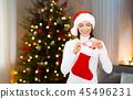 woman putting christmas gift box into stocking 45496231