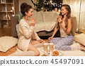 happy female friends eating waffles at home 45497091