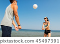 happy couple playing volleyball on summer beach 45497391