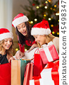 women in santa hats with gifts on christmas 45498347