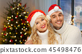 couple in santa hats over christmas tree lights 45498476