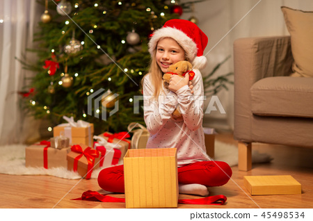 smiling girl in santa hat with christmas gift 45498534