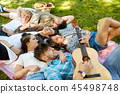 friends playing guitar and chilling at summer park 45498748