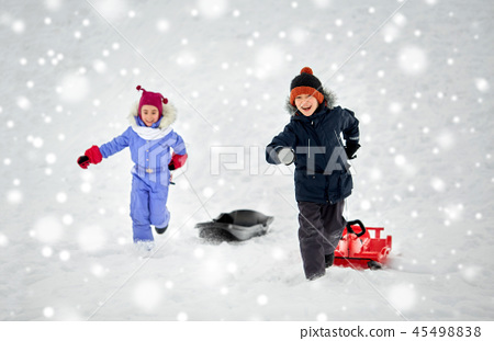 happy kids with sled having fun outdoors in winter 45498838