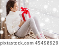 girl with christmas gift sitting on sill at window 45498929