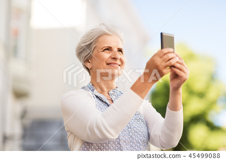 senior woman photographing by smartphone in city 45499088