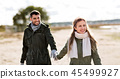 couple walking along autumn beach 45499927