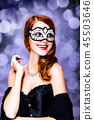 Style redhead girl in dark dress and mask 45503646