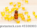 gold capsules of natural cosmetik for face and 1 ml bottle with essential oil on the wooden 45506903