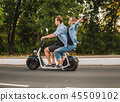 Lovely young couple driving electric bike during summer 45509102