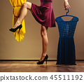 woman customer holding hangers with clothes 45511192