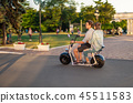 Lovely young happy couple driving electric bike 45511583