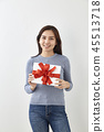 Young woman happy hold gift box in hands 45513718
