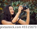 Beautiful Brunette Woman Taking a Picture Outdoor by Digital Camera 45515673