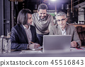 Pleased businessman looking at computer during conference 45516843