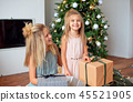 Two sisters with blond hair in luxurious dresses are sitting near the Christmas tree and looking at 45521905