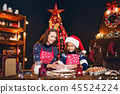 Merry Christmas and Happy Holidays. Mother and daughter cooking Christmas cookies. 45524224