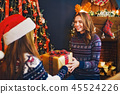Rear view from the back of a cheerful mom and her cute daughter girl exchanging gifts. 45524226