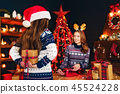 Rear view from the back of a cheerful mom and her cute daughter girl exchanging gifts. 45524228