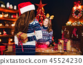 Rear view from the back of a cheerful mom and her cute daughter girl exchanging gifts. 45524230