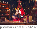 a happy family mother and child pack Christmas gifts 45524232