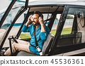 Cheerful man putting his headphones on while being in helicopter 45536361