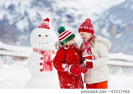 Child building snowman. Kids build snow man. 45537468