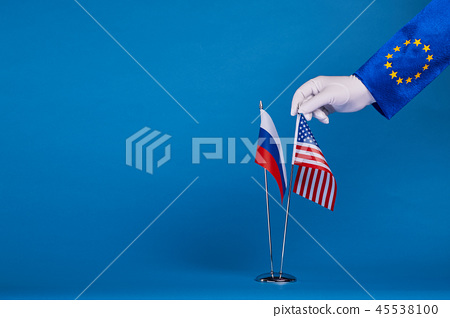 Two flags and hand on a blue background 45538100
