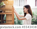 Asian woman put sticky memo paper note on parcel mail box and re 45543438
