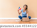 Young woman with French flag using a laptop computer 45544122