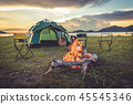 Camping tent with bonfire in green field meadow 45545346