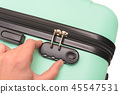Hand opens suitcase combination lock on suitcase. 45547531