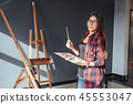 Young woman artist painting a picture in studio 45553047