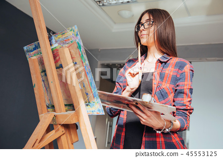 Pretty Pretty Girl artist paints on canvas painting on the easel. Studio black background. Long hair 45553125