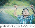 The boy stands behind the fence. 45556912