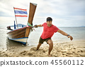 Man with stubble is pulling wooden boat by rope on sand beach 45560112