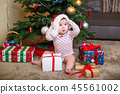 Happy cute baby girl in Santa Claus hat holding Christmas gifts at christmas tree at home 45561002