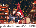 holidays, family and people concept. Happy mother and little girl in santa helper hat with sparklers 45563898
