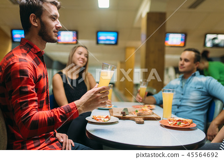 Friends drinks and eats pizza in bowling club 45564692