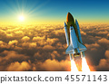 Flight Of The Space Shuttle Above The Clouds In The Rays Of The Rising Sun. 45571143