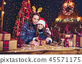 a happy family mother and child pack Christmas gifts 45571175