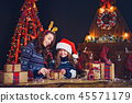 a happy family mother and child pack Christmas gifts 45571179