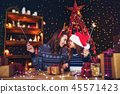 holidays, family and people concept. Happy mother and little girl in santa helper hat with sparklers 45571423