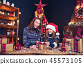 a happy family mother and child pack Christmas gifts 45573105