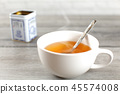 Cup of hot amber tea with steam, with metal tin 45574008