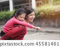 young daughter on a piggy back ride with mother 45581461