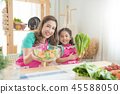 mother and daughter cooking in kitchen 45588050