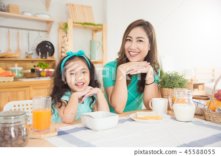mother and daughter having breakfast together  45588055