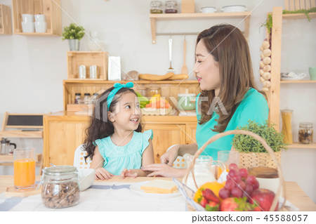 mother and daughter sitting at breakfast table  45588057